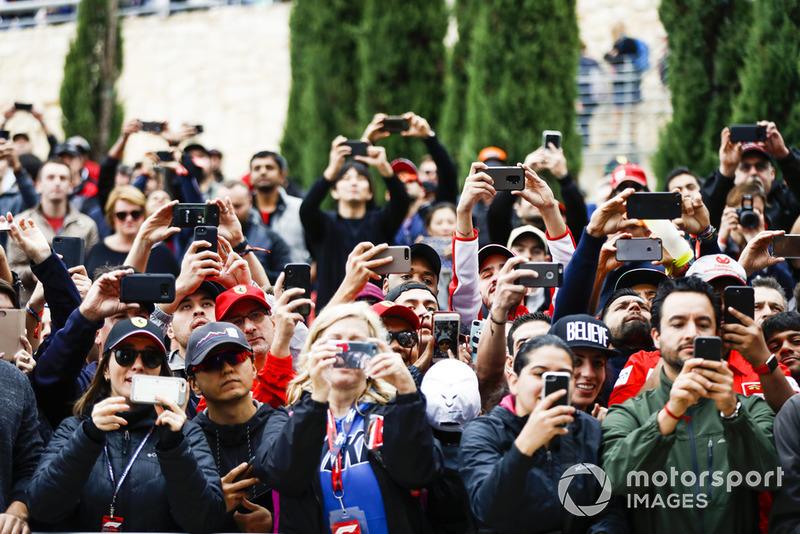 Los aficionados toman fotos de los conductores con sus teléfonos móviles.