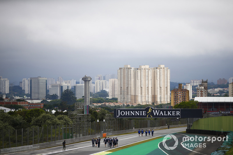 Vista de Sao Paulo detrás del circuito, en primer plano Pierre Gasly, Toro Rosso y los miembros del equipo caminan por el circuito, junto con Sergio Pérez, Force India