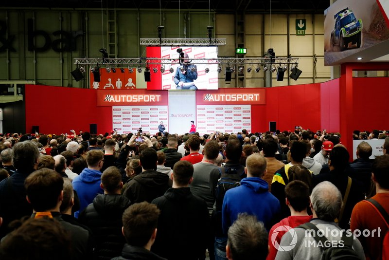 A large crowd gathers to listen to presenter Stuart Codling interview Charles Leclerc, Ferrari on the Autosport stage