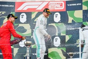 Sebastian Vettel, Ferrari, 2nd position, Valtteri Bottas, Mercedes AMG F1, 1st position, and Lewis Hamilton, Mercedes AMG F1, 3rd position, spray Champagne on the podium