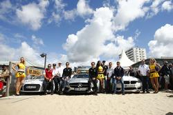 Les pilotes posent sur la plage avec les voitures de sécurité