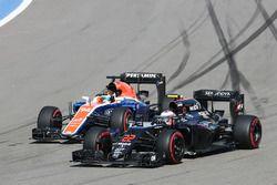 Jenson Button, McLaren MP4-31 and Rio Haryanto, Manor Racing MRT05 battle for position