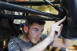 Un mécanicien travaille sur la suspension avant de la McLaren MCL32