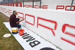 A painter finishes a Porsche banner on the start/finish straight