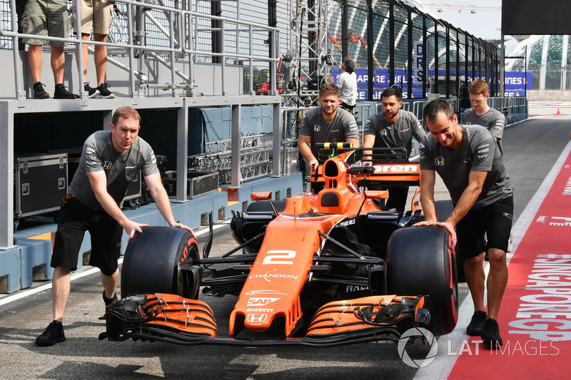 I meccanici McLaren spingono la McLaren MCL32
