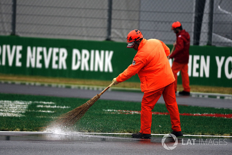 Marshal sweeps water off the track