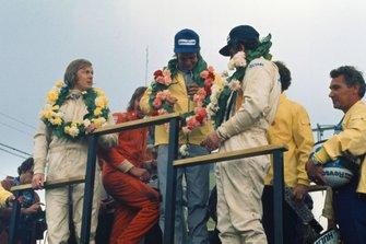 Podio: segundo lugar Ronnie Peterson, Lotus, ganador de la carrera Peter Revson, McLaren, tercer lugar Denny Hulme, McLaren, con James Hunt.