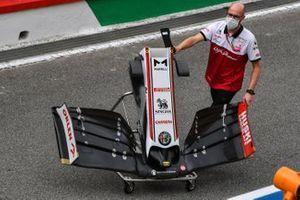 An Alfa Romeo Racing mechanic wheels a front wing along the pitlane