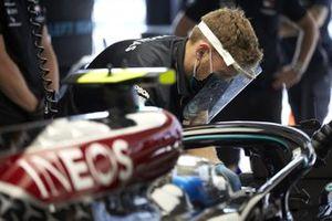 Mechanics work on the car of Valtteri Bottas, Mercedes F1 W11, in the garage