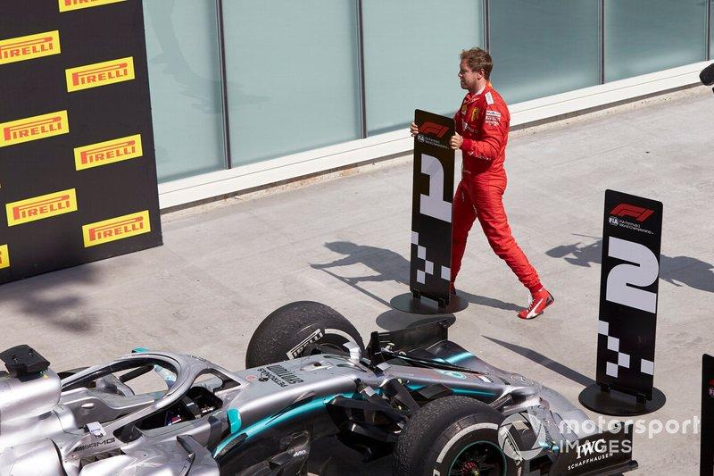 Sebastian Vettel, Ferrari, 2º lugar, cambia los letreros de posición en protesta por una penalización que le costó la victoria.