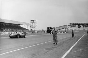 A mechanic holds out a pitboard as Juan Manuel Fangio, Ferrari D50 passes