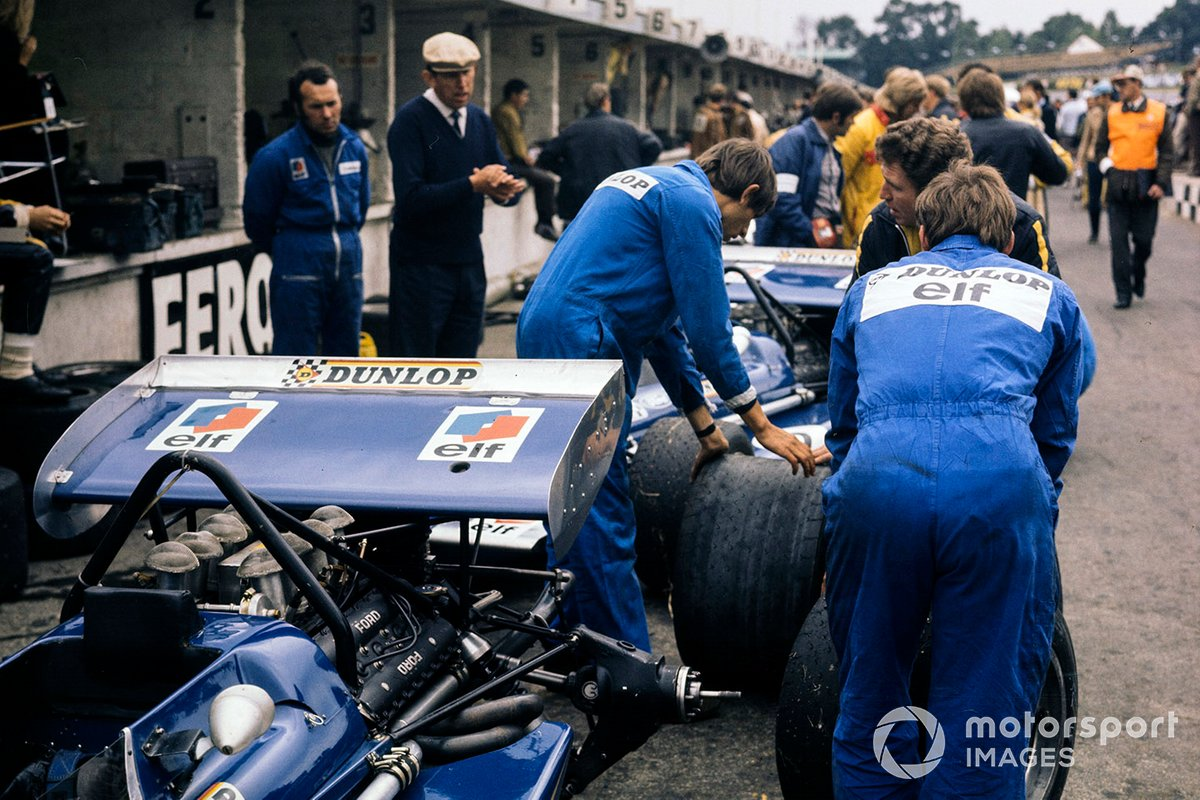 Tyrrell mechanics change the tyres on their cars in the pit lane as overseen by Ken Tyrrell