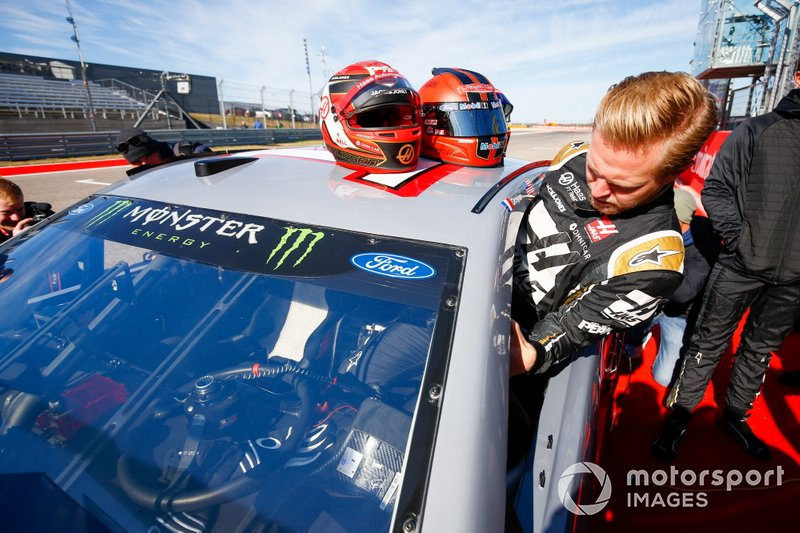 Kevin Magnussen, Haas F1, gets into the car of NASCAR Cup driver Tony Stewart