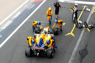 Mechanics push back Lando Norris, McLaren in the pit lane