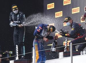 Lewis Hamilton, Mercedes, 2nd position, Max Verstappen, Red Bull Racing, 1st position, Lando Norris, McLaren, 3rd position, and the Red Bull trophy delegate spray Champagne