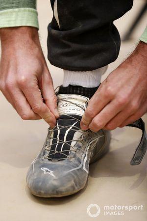 Jenson Button, JBXE Extreme-E Team, ties his race boots