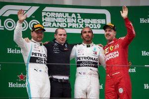 Valtteri Bottas, Mercedes AMG F1, deuxième, un membre de l'équipe Mercedes, Lewis Hamilton, Mercedes AMG F1, vainqueur, et Sebastian Vettel, Ferrari, troisième, sur le podium