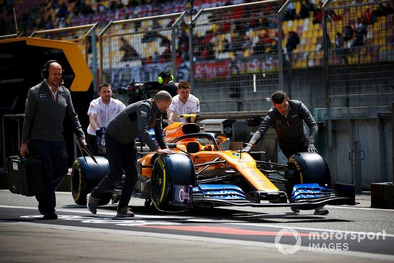 McLaren mechanics move the car of Lando Norris, McLaren MCL34, through the pit lane