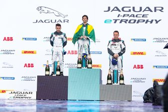 Sérgio Jimenez, 1st position, on the podium, draped in a Brazilian flag. Alongside is Bryan Sellers, 2nd position, Simon Evans, 3rd position