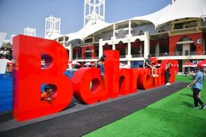 Children play on a giant Bahrain sign