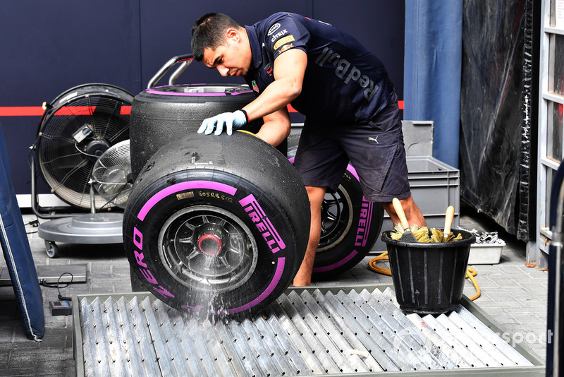 Red Bull Racing mechanics washes wheel rim and Pirelli tyre