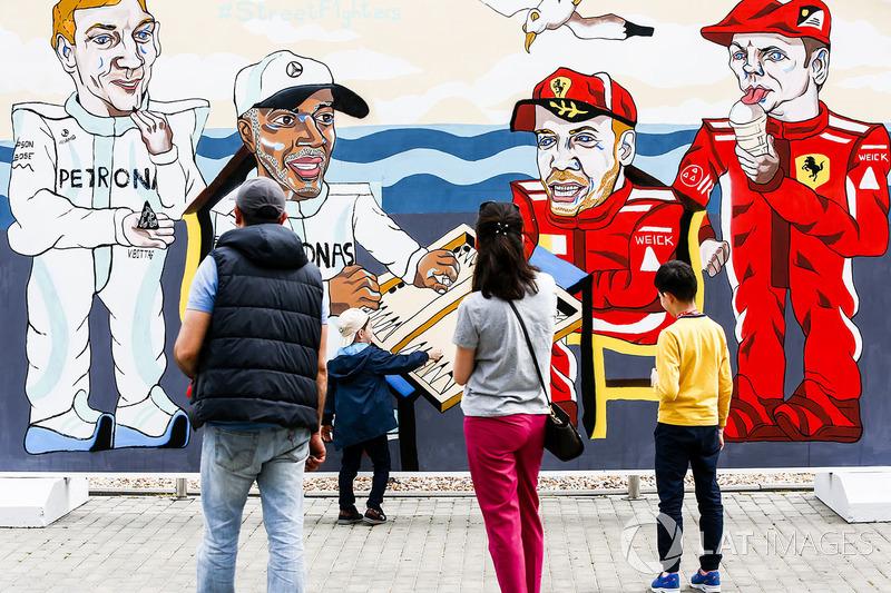 Los fanáticos miran obras de arte que representan a Valtteri Bottas, Mercedes AMG F1, Lewis Hamilton, Mercedes AMG F1, Sebastian Vettel, Ferrari y Kimi Raikkonen, Ferrari, jugando al backgammon