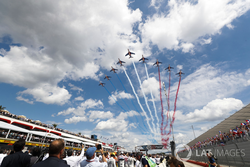The French Air Force Aerobatics team, La Patrouille de France, overfly the grid in their Dassault Alpha Jet Es