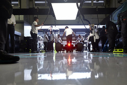 Engineers return a Mercedes AMG F1 W09 to their garage