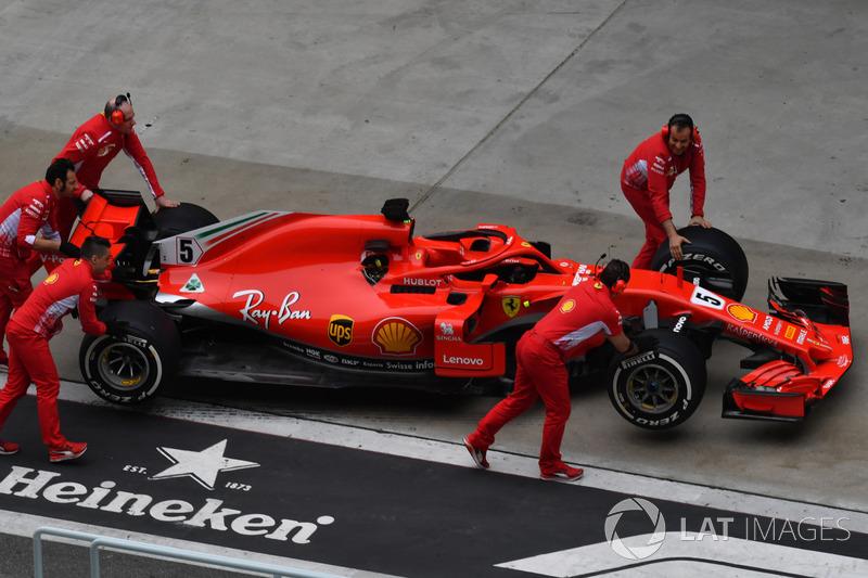 Ferrari mechanics with Ferrari SF71H in pit lane