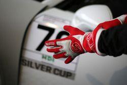 Un pilota infila i guanti accanto alla Porsche 911 GT3 Guest Car