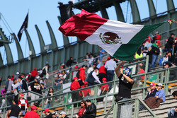 Fans in the grandstand and a man with a Mexican flag