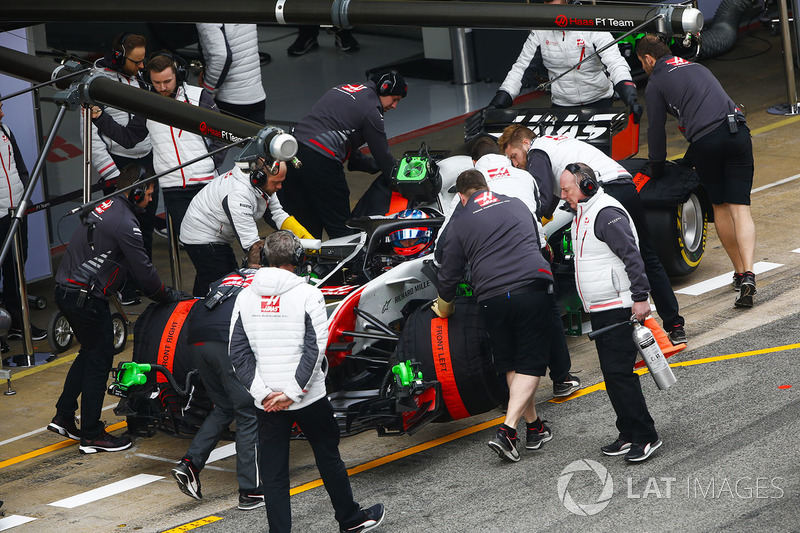 Romain Grosjean, Haas F1 Team VF-18, is attended to by mechanics in the pit lane