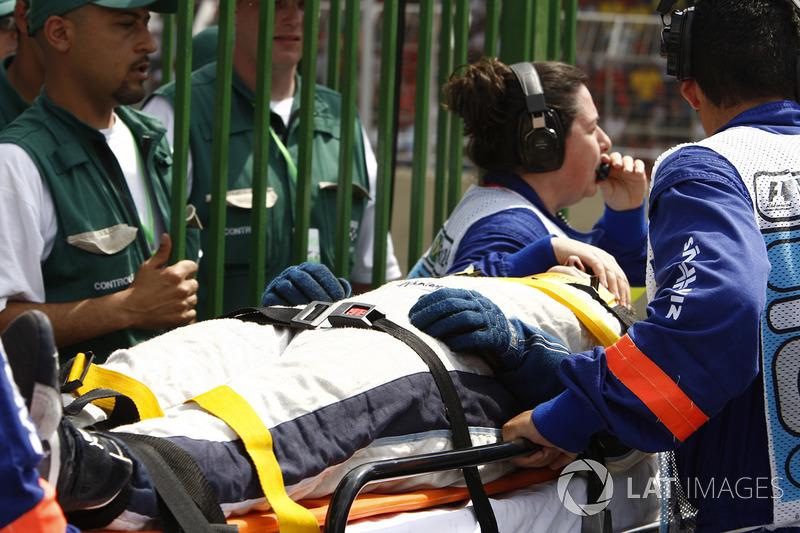 Un mecánico de Williams en camilla después de ser golpeado por Kazuki Nakajima, Williams FW29 durante una parada en boxes