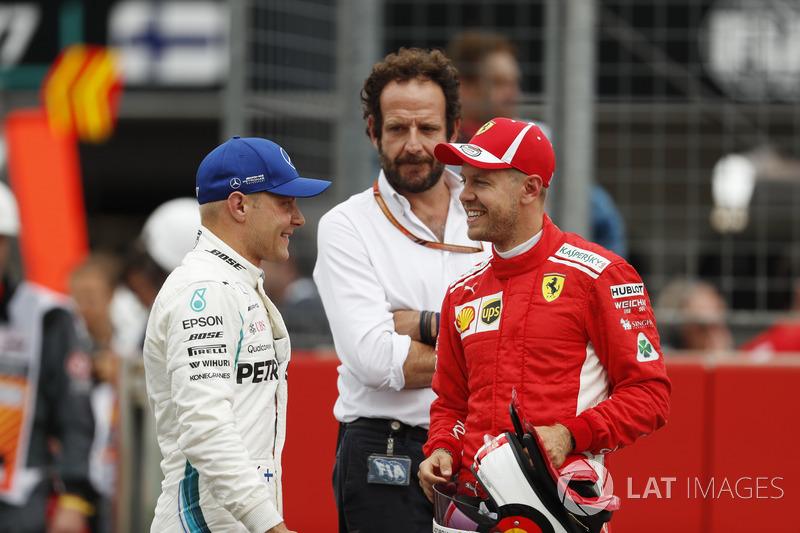 Pole sitter Sebastian Vettel, Ferrari, talks to Valtteri Bottas, Mercedes AMG F1