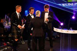 Derek Warwick reçoit un trophée des mains de Lando Norris et George Russell