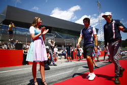 Grid Girls in national costume flank the drivers parade as Lance Stroll, Williams Racing, and Esteban Ocon, Force India, pass