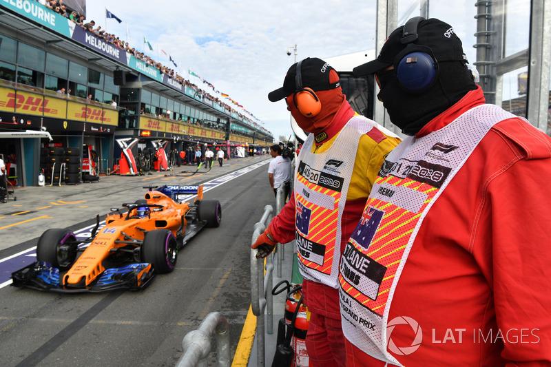 Marshal mengawasi Fernando Alonso, McLaren MCL33 di pit lane