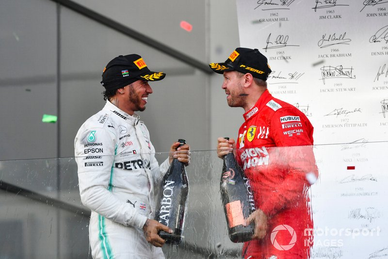 Lewis Hamilton, Mercedes AMG F1, 2nd position, and Sebastian Vettel, Ferrari, 3rd position, celebrate on the podium