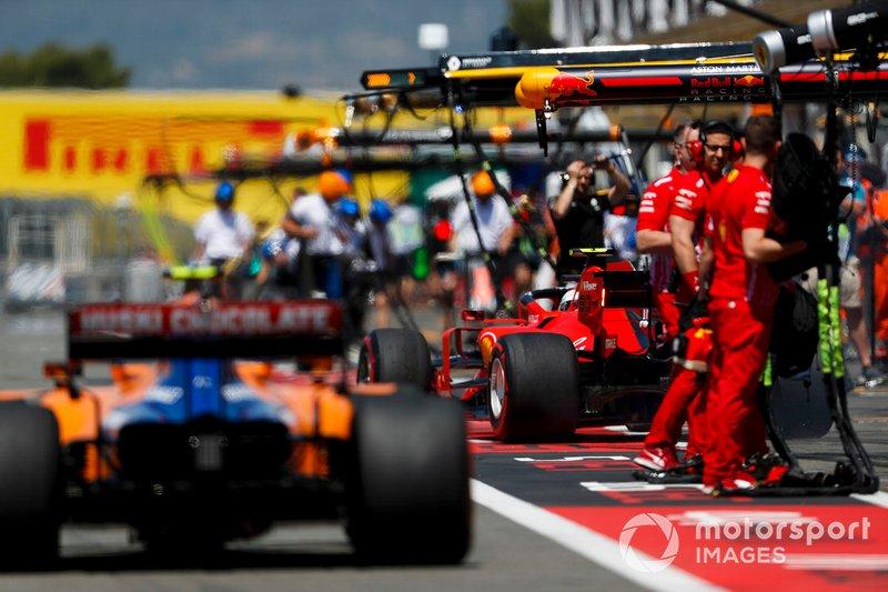 Lando Norris, McLaren MCL34, y Charles Leclerc, Ferrari SF90 en pit lane