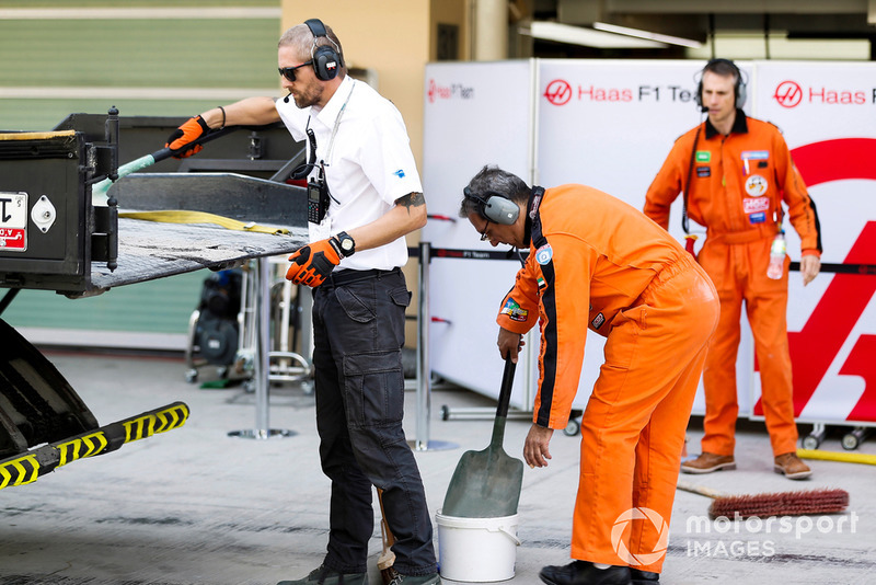 Marshals and Haas team members help return the Pietro Fittipaldi Haas F1 Team VF-18 to the pits on a truck