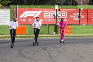 Lewis Hamilton, Mercedes-AMG F1, rides the track on an electric scooter with team mates