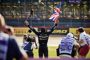 Lewis Hamilton, Mercedes , 1st position, celebrates with a Union flag after the race