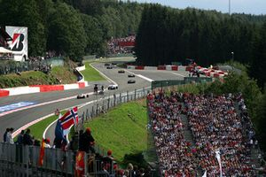The cars stream through Eau Rouge