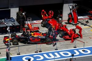 Mechanics in the pit lane with the cars of Max Verstappen, Red Bull Racing RB16, and Sebastian Vettel, Ferrari SF1000