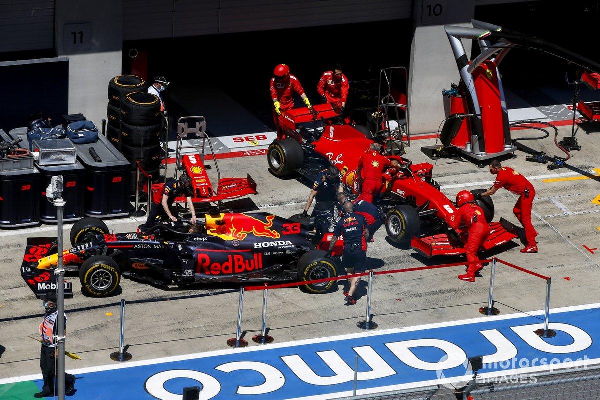 Mecánicos en el pit lane con los coches de Max Verstappen, Red Bull Racing RB16, y Sebastian Vettel, Ferrari SF1000