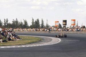 Jacky Ickx, Ferrari 312B, passes an unruly crowd of spectators