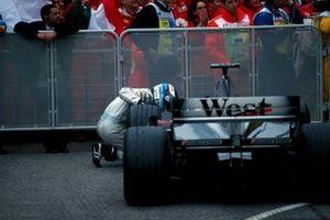 Mika Hakkinen, Mclaren MP4-15, looks for damage to his car