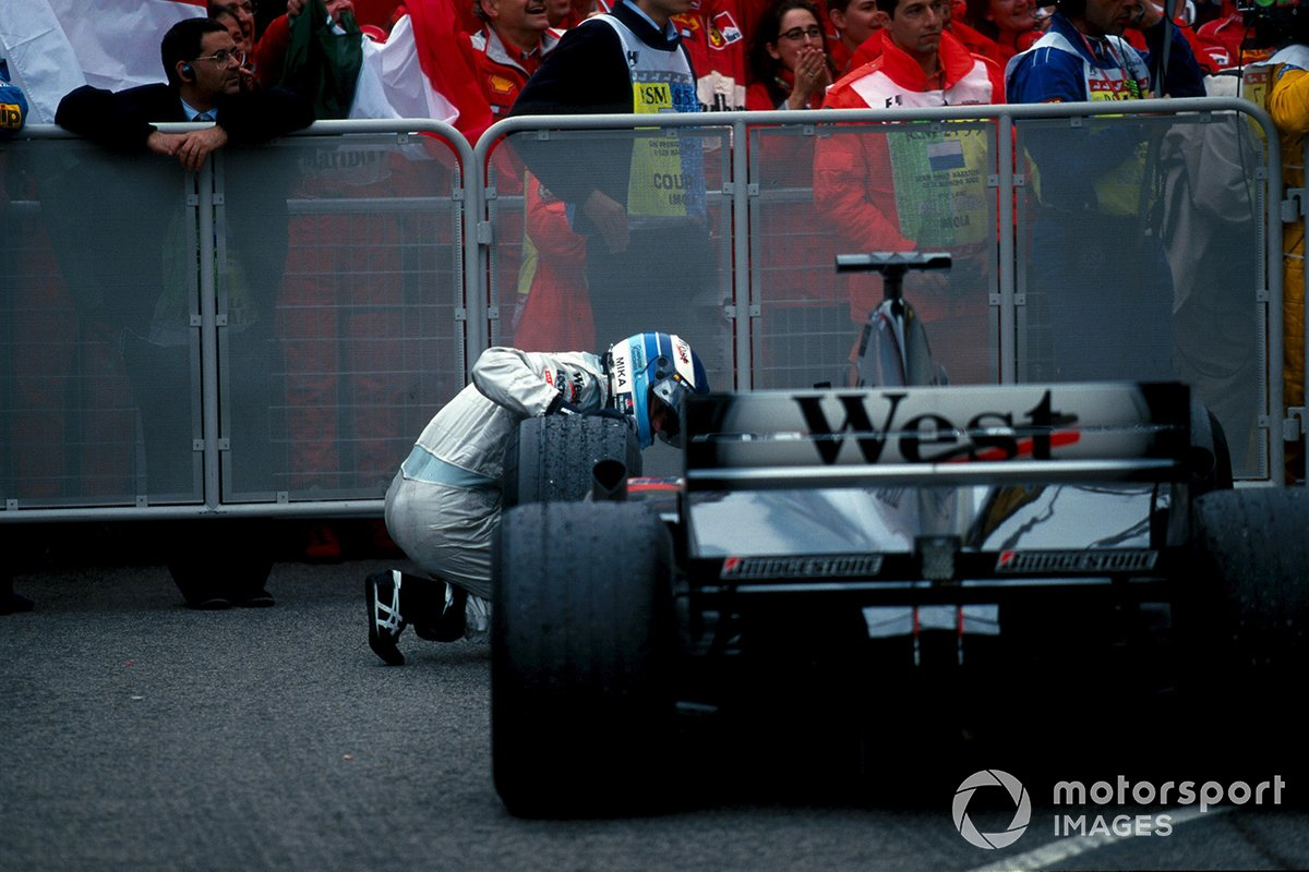 Mika Hakkinen, Mclaren MP4-15, looks for damage to the floor of his car