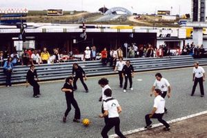 Brabham and Williams mechanics play football on the grid. Nelson Piquet sits on the pit wall looking on.