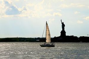 A yacht sails past the Statue of Liberty